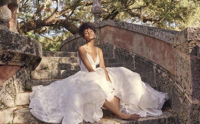 Bride Sitting on Steps Wearing Modern Princess Wedding Dress Called Yuri by Maggie Sottero