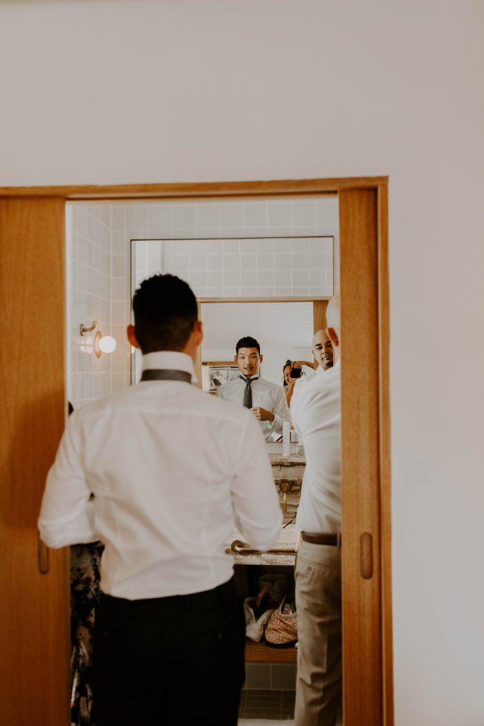 Groom Putting on Wedding Attire for Beach Wedding