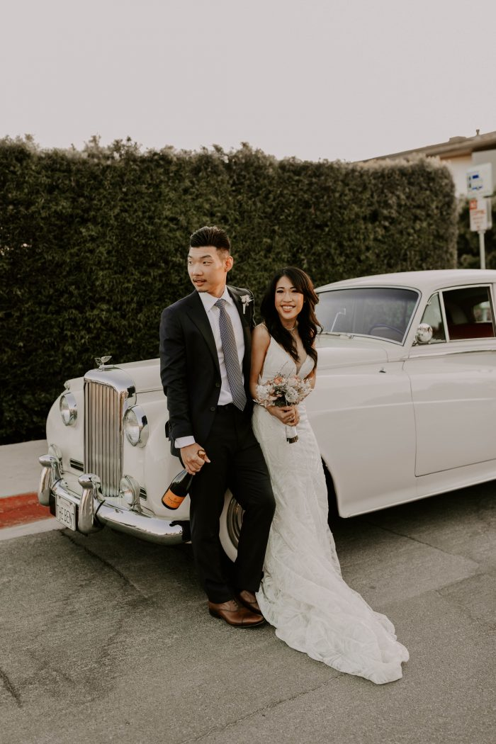 Groom in Front of Vintage Car with Bride Wearing Sparkly Sheath Wedding Dress Called Elsie by Rebecca Ingram
