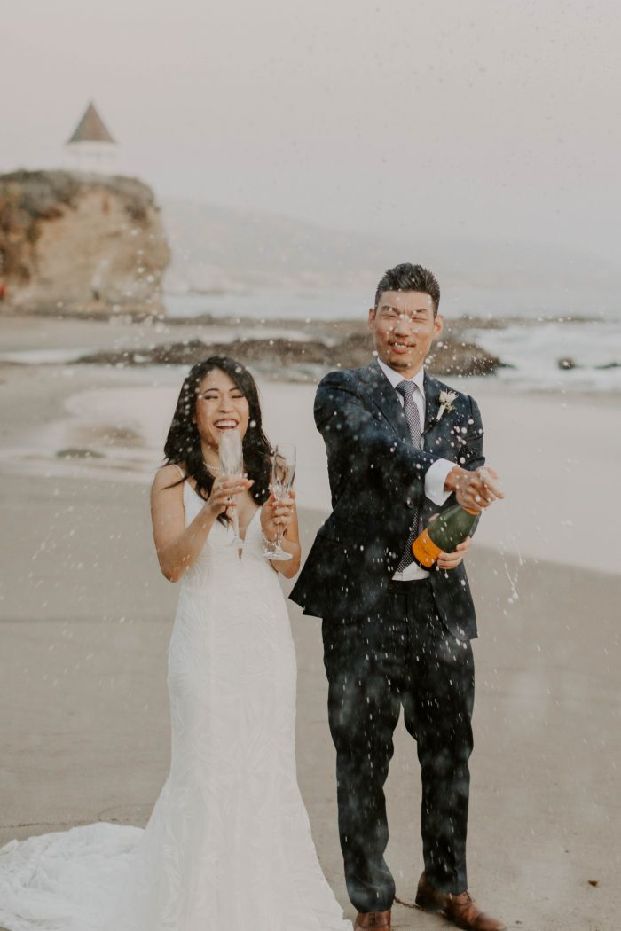 Bride and Groom Popping Champagne Bottle After Beach Elopement Ceremony