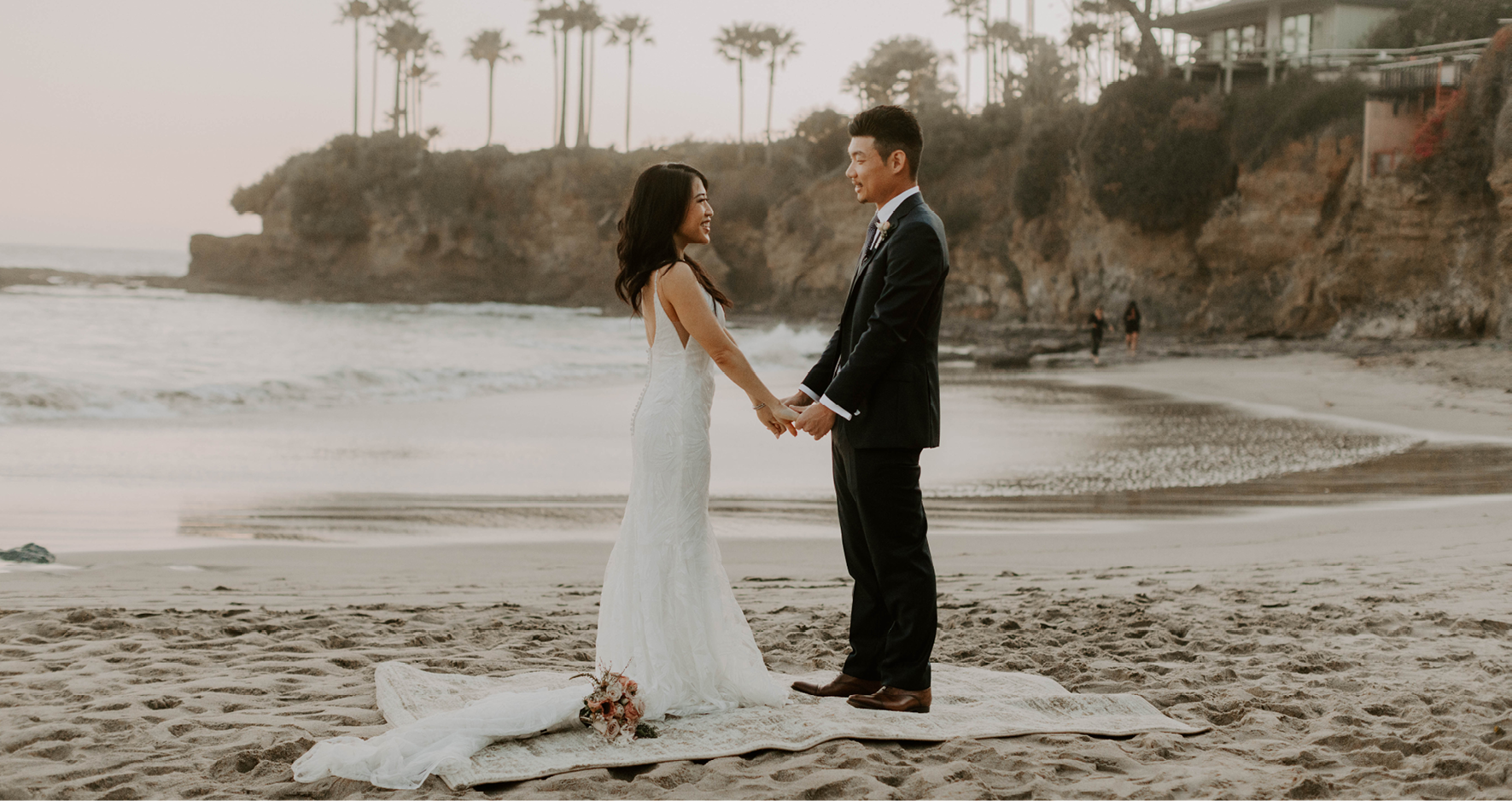 Real Bride and Groom Holding Hands at Intimate and Casual Beaching Wedding While Brides Wearing a Maggie Sottero Wedding Dress