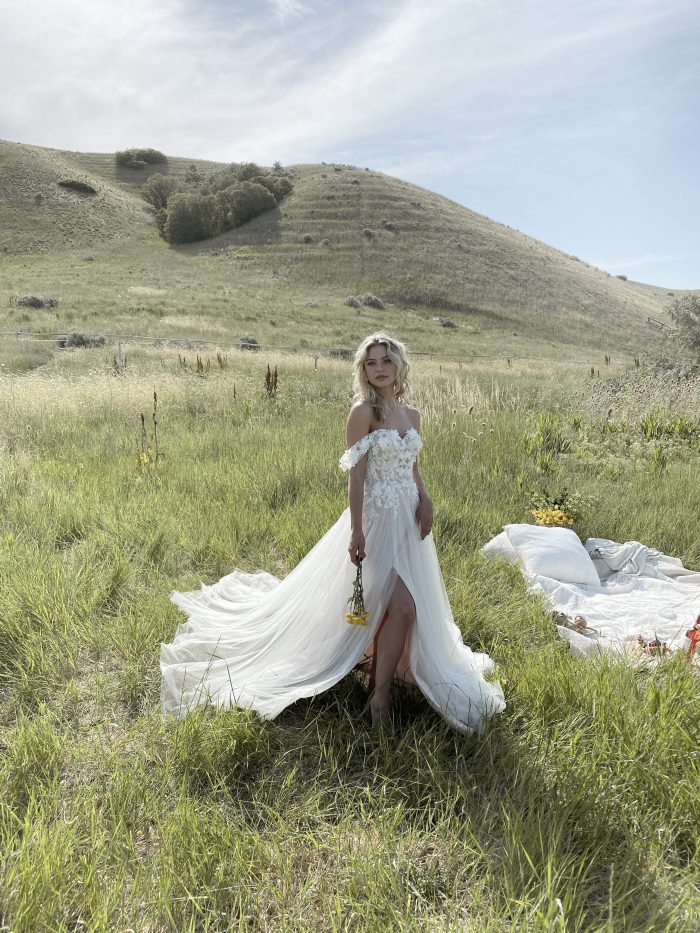 Bride in Field Wearing 3-D Floral Cottagecore Wedding Gown Called Mirra by Maggie Sottero