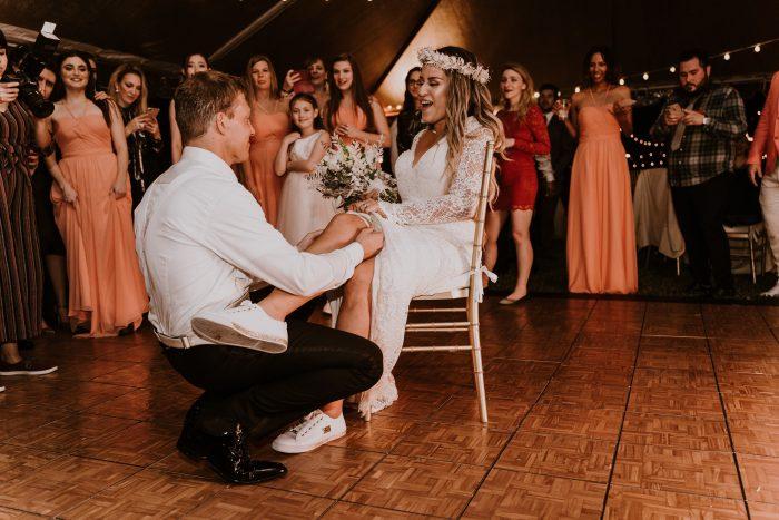 Wedding Garter Tradition of Groom Taking Garter off of Bride's Leg During Reception