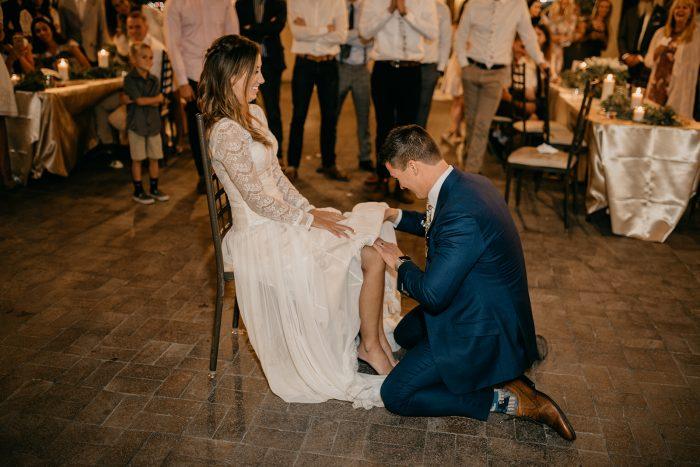 Groom Taking Wedding Garter off of Bride's Leg During Wedding Reception