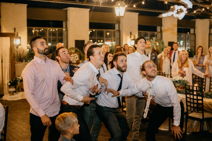 Groomsmen Catching Wedding Garter During Wedding Garter Toss