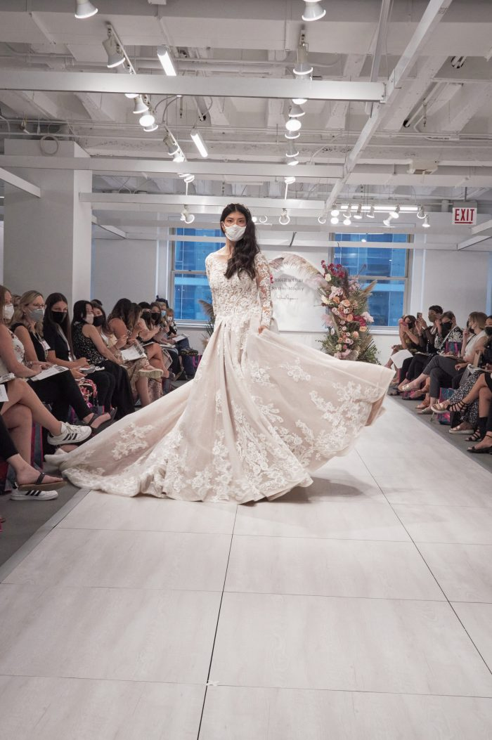 Model Walking Down the Runway at Chicago Bridal Market Wearing Princess Ball Gown Wedding Dress with Long Sleeves Called Norvinia Lynette by Sottero and Midgley